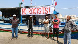 """Des pêcheurs protestent contre le possible accostage du """"C-Star"""", un bateau affrété par des militants d'extrême droite pour lutter contre l'arrivée des migrants en Europe, le 6 août 2017 au port de Zarzis (Tunisie). (FATHI NASRI / AFP)"""