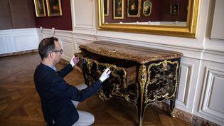 Le directeur du Musée National du château de Versailles, Laurent Salome, inspecte la magnifique commode du XVIIIe siècle que vient d'acquérir le Musée pour 4 millions d'euros. Le meuble avait disparu pendant la Révolution française. (CHRISTOPHE ARCHAMBAULT / AFP)