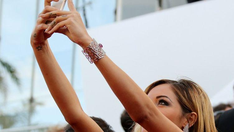Nabilla Benattia pose pour un selfie au 67e festival de Cannes (Alpes-Maritimes), le 18 mai 2014. (LOIC VENANCE / AFP)