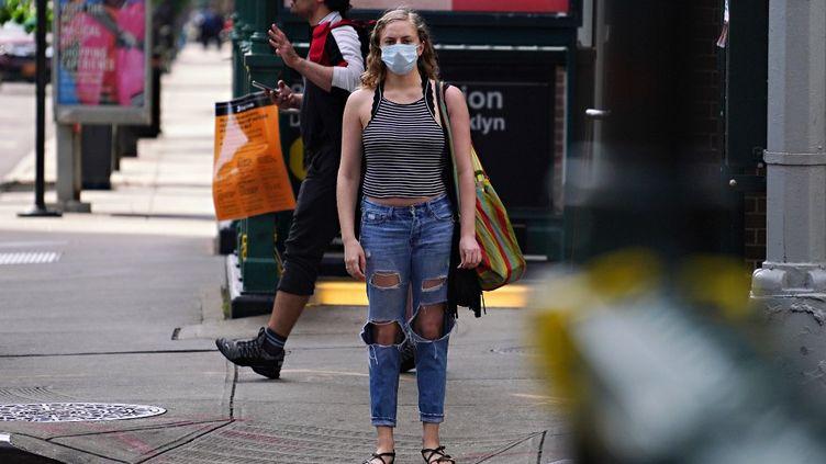 Une femme portant un masque de protection marche dans la rue à New York, le 27 mars 2020. (CINDY ORD / GETTY IMAGES NORTH AMERICA / AFP)