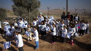 Des enfants israéliens avec leurs drapeaux au sein de la colonie de Gitit, dans la vallée du Jourdain, le 2 janvier 2014. (RONEN ZVULUN / REUTERS)