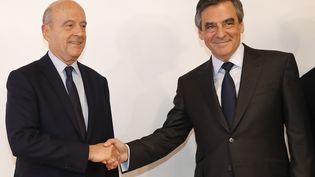 Alain Juppé (G) et François Fillon se serrent la main au siège de la Haute Autorité de la primaire à droite, à Paris, le 27 novembre 2016. (FRANÇOIS GUILLOT / AFP)