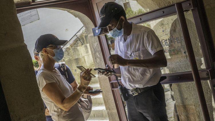 Un employé d'un lieu culturel à Nantes (Loire-Atlantique) contrôle le pass sanitaire des visiteurs, le 21 juillet 2021. (ESTELLE RUIZ / HANS LUCAS / AFP)