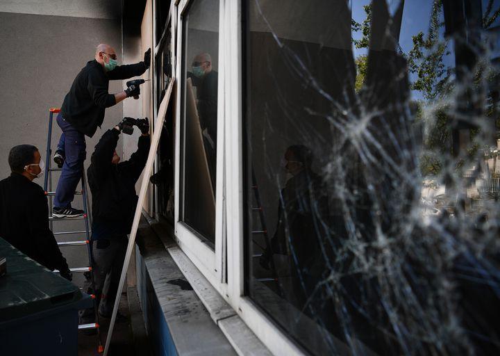 Des employés réparent la vitre d'une école primaire de Gennevilliers (Hauts-de-Seine) qui a été la cible d'un caillassage, le 22 avril 2020. (CHRISTOPHE ARCHAMBAULT / AFP)