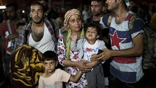 Une famille attend de pouvoir embarquer sur un ferry, le 7 septembre 2015, sur l'île grecque de Lesbos. (ANGELOS TZORTZINIS / AFP)