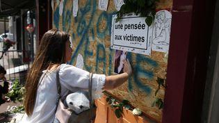 Une jeune femme rend hommage auxvictimesde l'incendiedubar Cuba Libre, le 6 août 2017 à Rouen. (CHARLY TRIBALLEAU / AFP)