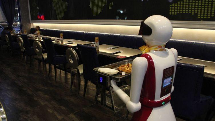 Le robot, qui mesure 1,60 m de haut et est rechargé une fois par jour (pendant quatre heures), apporte lui-même leurs commandes aux clients de ce restaurant. Dont l'ambiance n'est pas sans évoquer celle des peintures de l'artiste américain Edward Hopper... Le personnel humain place un plat sur le plateau de la machine et indique la table à livrer par le biais d'une télécommande. L'initiative de Binzhou n'est pas la première du genre en Chine. A Harbin (nord-ouest), un tel restaurant a ouvert ses portes en 2012. Là, le robot peut préparer des nems, servir les clients, débarrasser les tables, faire la vaisselle. Le directeur de l'établissement explique que ces machines sont moins exigeantes que les humains. Et ne rechignent pas à travailler le dimanche. (SIPA ASIA - SIPA)