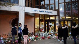 Des passants déposent devant des fleurs à l'entrée du collège de Conflans-Sainte-Honorine où enseignait la victime, le 17 octobre 2020. (BERTRAND GUAY / AFP)