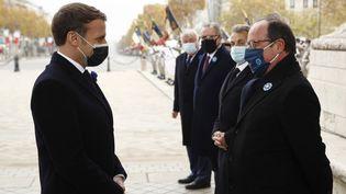 Le président Emmanuel Macron et son prédécesseur François Hollande, sous l'Arc de triomphe à Paris, le 11 novembre 2020. (YOAN VALAT / AFP)