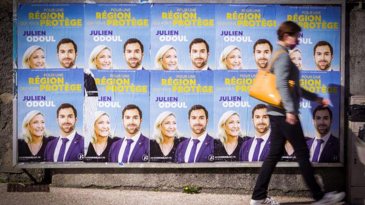 Une personne passe devant des affiches de Julien Odoul, candidat du Rassemblement national aux élections régionales de Bourgogne-Franche-Comté, le 4 avril 2021 à Montbéliard. (LIONEL VADAM  / MAXPPP)