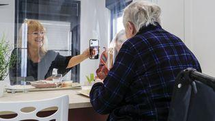 Un résident d'un Ehpad de Villeneuve-Saint-Georges (Val-de-Marne) reçoit ses proches, le 12 novembre 2020. (GEOFFROY VAN DER HASSELT / AFP)