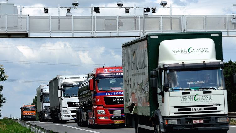"""Des poids-lourds passent sous un portique qui leur permet de """"pointer"""" pour l'écotaxe, le 27 juin 2013 à Armentières (Nord). (PHILIPPE HUGUEN / AFP)"""