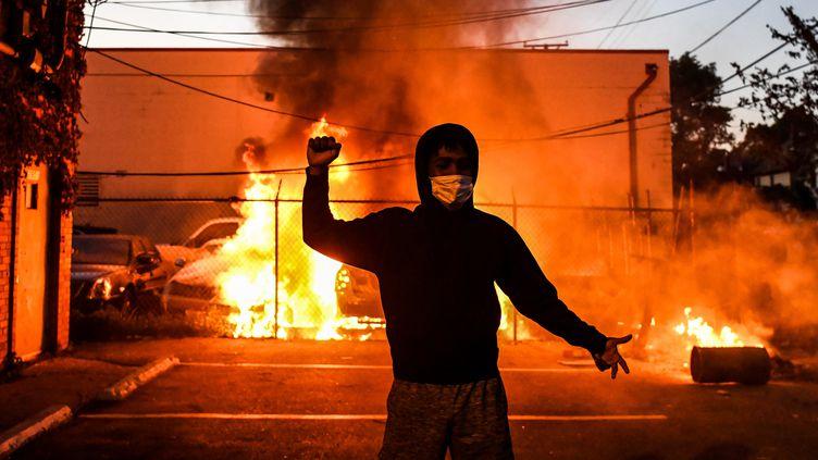 Un jeune manifestant derrière une voiture qui brûle à Minneapolis, le 29 mai 2020. (CHANDAN KHANNA / AFP)