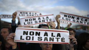 """Une femme tient une pancarte """"non à la loi santé"""", durant une manifestation des médecins à Rennes (Ile-et-Vilaine), le 13 novembre 2015. (DAMIEN MEYER / AFP)"""