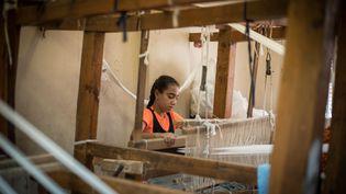 Une jeune fille d'un quartier pauvre de la banlieue du Caire (Egypte) travaille surun métier à tisser, le 2 août 2018. (CHLOE SHARROCK / LE PICTORIUM / MAXPPP)