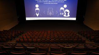 La salle vide du cinéma UGC Paris 19. Un message a l'écran demande aux spectateurs de laisser un siège entre chaque groupe. (THOMAS COEX / AFP)