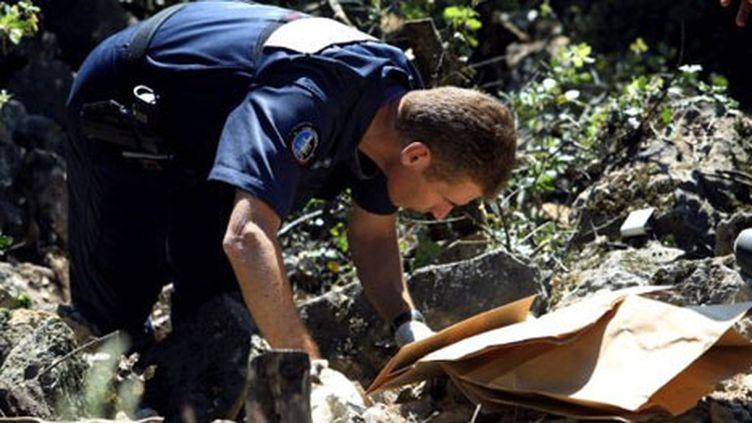Un gendarme effectue, le 17 mai 2011 à Aups, des fouilles sur les lieux où le corps de Colette Deromme a été retrouvé. (AFP/Sebastien Nogier)
