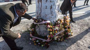 Un homme dépose des fleurs le 19 mars 2015 près du musée du Bardo à Tunis (Tunisie), où a eu lieu une attaque terroriste, la veille. (AMINE LANDOULSI / ANADOLU AGENCY / AFP)