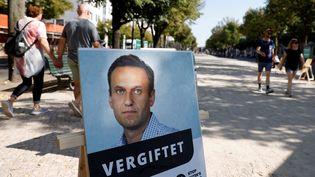 """Une affiche avec une photo du leader de l'opposition russe Alexei Navalny,etle titre """"Empoisonné"""", devant l'ambassade russe à Berlin, en Allemagne, lors d'une manifestation, le 23 septembre 2020. (ODD ANDERSEN / AFP)"""