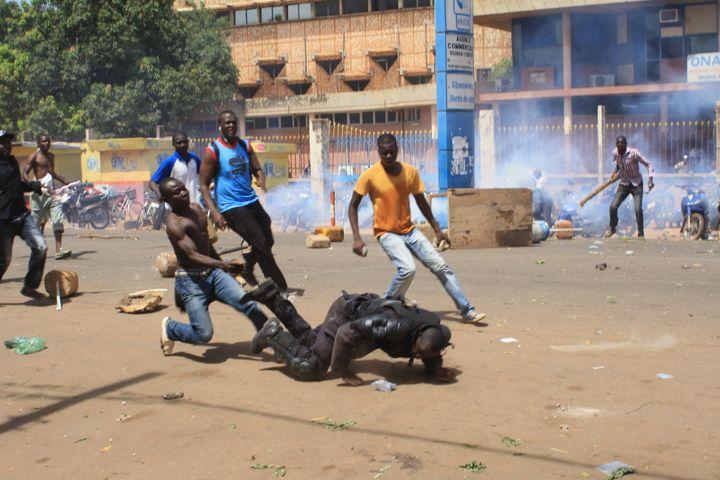 Des manifestants s'attaquent à un policier à Ouagadougou (Burkina Faso), le 28 octobre 2014, à l'issue d'une manifestation contre le président. (CITIZENSIDE / JEAN DANIEL GYGER / AFP)