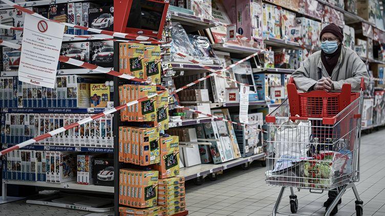 Une cliente d'un supermarché passe devant un rayon de produits non essentiels fermé, le 4 novembre 2020. (PHILIPPE LOPEZ / AFP)