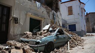 Une voiture sous les décombres d'un immeuble, détruit dans un séisme, à Lesbos (Grèce), le 13 juin 2017. (ALI ATMACA / ANADOLU AGENCY / AFP)