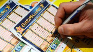 Un homme remplit un ticket de loterie Euro Millions, le 5 novembre 2012 à Tours (Indre-et-Loire). (ALAIN JOCARD / AFP)