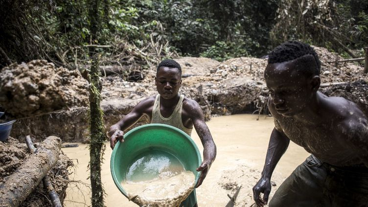 Des hommes recherchent des poussières d'or dans une mine artisanale en RDC, dans la province de l'Ituri. En une semaine de travail, ils vont récupérer au mieux six grammes d'or. (JOHN WESSELS / AFP)
