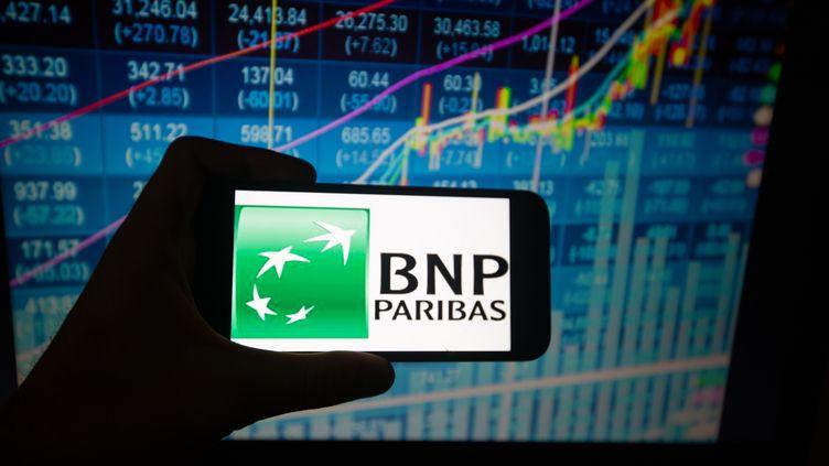 Le logo de la banque française BNP Paribas s'affiche sur un téléphone portable, le 28 août 2018. (ALEXANDER POHL / NURPHOTO / AFP)