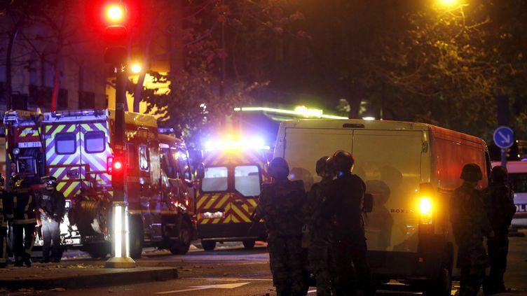 Des policiers encadrent une intervention des pompiers, le 14 novembre 2015, à Paris, près du Bataclan. (CHRISTIAN HARTMANN / REUTERS)