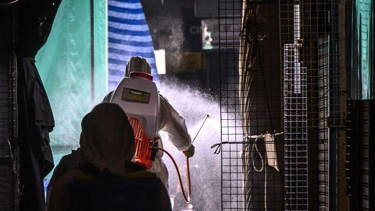 Des brigades désinfectent les allées du marché Chatuchak à Bangkok, le 23 mars 2020 (MLADEN ANTONOV / AFP)