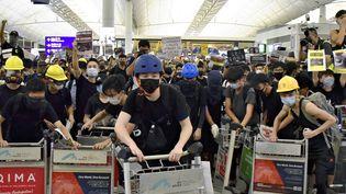 Des manifestants bloquent le hall des départs à l'aéroport international de Hong Kong (Chine), le 13 août 2019. (SHIOMI KADOYA / YOMIURI / AFP)
