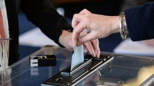 Un électeur glisse un bulletin dans l'urne. (MAXPPP)