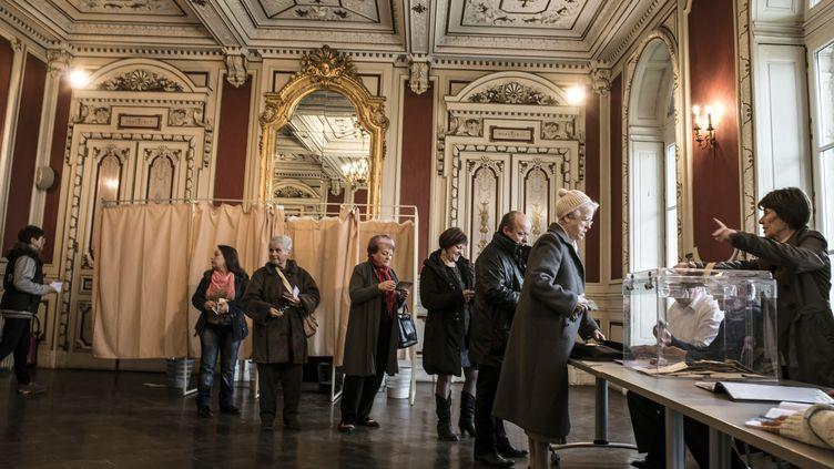 Des électeurs attendent de déposer leur bulletin dans l'urne à Tullins (Isère), le 22 mars 2015, lors du premier tour des élections départementales. (JEAN-PHILIPPE KSIAZEK / AFP)