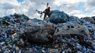 Un homme en train de trier des bouteilles en plastique sur la décharge de Kibarani à Mombasa, au Kenya,le 3 juin 2018(photo d'illustration) (ANDREW KASUKU / AFP)