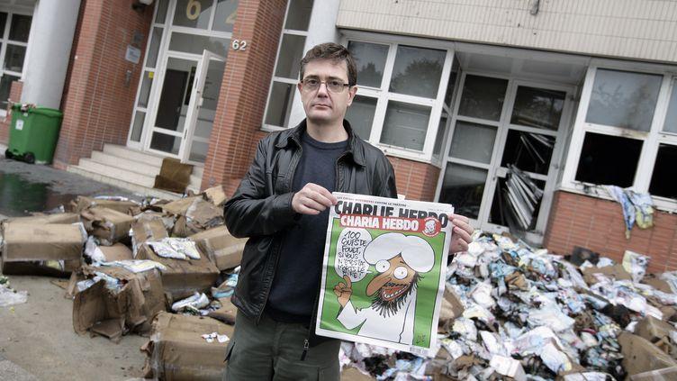 Charb, le directeur de la publication de Charlie Hebdo, devant les locaux incendiés de l'hebdomadaire satirique, à Paris, le 2 novembre 2011. (ALEXANDER KLEIN / AFP)