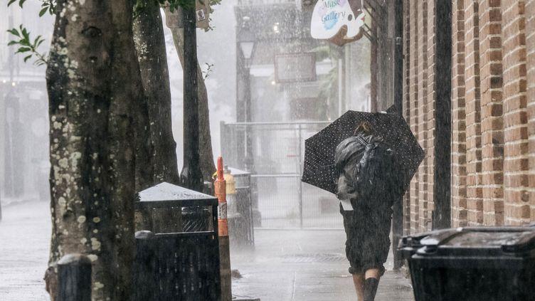 Une passante sous les fortes pluies qui ont frappé la Nouvelle-Orléans dimanche 29 août, avant l'arrivée de l'ouragan Ida en Louisiane. (BRANDON BELL / GETTY IMAGES NORTH AMERICA / AFP)