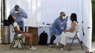 Des agents de santé administrent un test antigénique Covid-19 à des visiteurs près de la Tour Eiffel à Paris, le 21 juillet 2021. (BERTRAND GUAY / AFP)