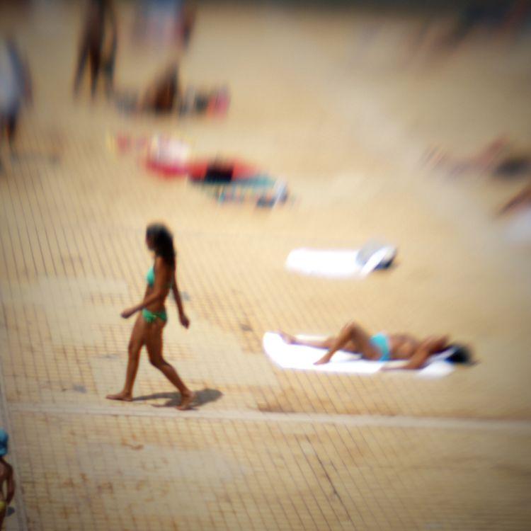 Plage artificielle d'une piscine en plein air, à Lyon (Rhône). En pleine canicule, les enfants souffrent de la chaleur même sous un parasol. (JEAN-PHILIPPE KSIAZEK / AFP)