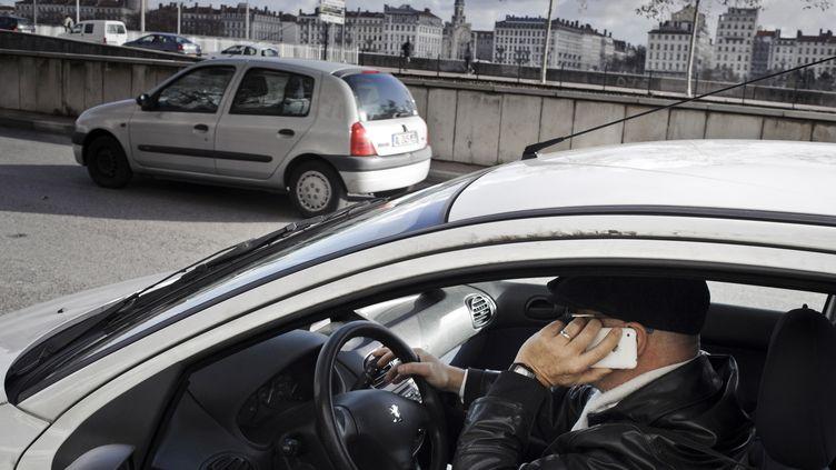 Un homme téléphone au volant, le 4 janvier 2012, à Lyon. (JEAN-PHILIPPE KSIAZEK / AFP)