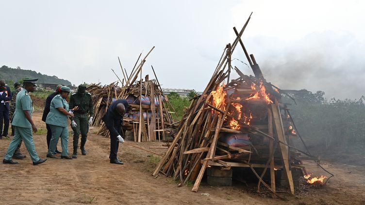 Le ministre ivoirien des Eaux et Forêts, Alain Richard Wonwahi (au centre), met le feu à des sacs d'écailles de pangolin saisis auprès de braconniers en 2017 et 2018 et incendiés le 3 mars 2020 dans la banlieue d'Abidjan. (ISSOUF SANOGO / AFP)