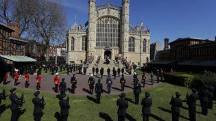 Le cercueil a ensuite été accueilli par les sifflements des pipes des marines, avant d'être porté dans la chapelle Saint-George, pour l'office religieux. Il était attendu en haut des marches par l'archevêque de Canterbury,Justin Welby,et le doyen de Windsor, David Conner. Un coup de canon a retenti pour annoncer une minute de silence dans tout le pays. (KIRSTY WIGGLESWORTH / AFP)