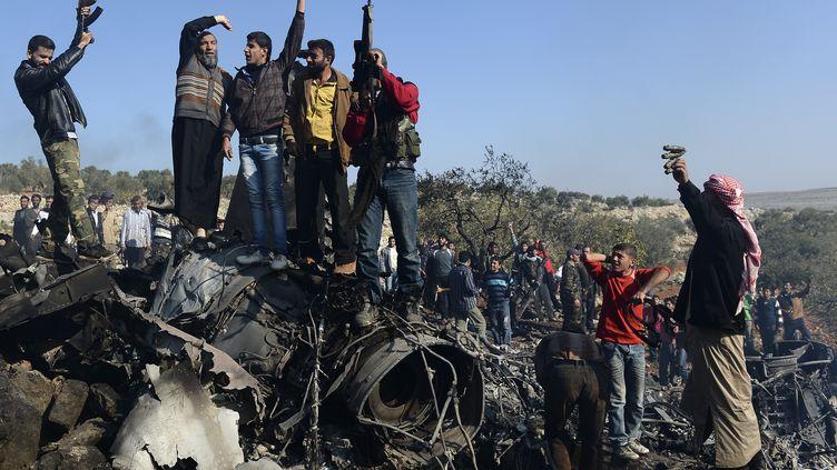 Des rebelles syriens en liesse sont juchés sur les débris d'un avion de l'armée de Bachar Al-Assad abattu dans la région de Darat Izza, mercredi 28 novembre 2012. (FRANCISCO LEONG / AFP)