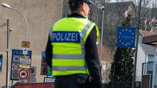 Une policière allemande surveille la frontière franco-allemande à Petite-Rosselle (Moselle), pour ne livrer passage qu'aux seuls travailleurs frontaliers, le 20 mars 2020. (OLIVER DIETZE / DPA / AFP)