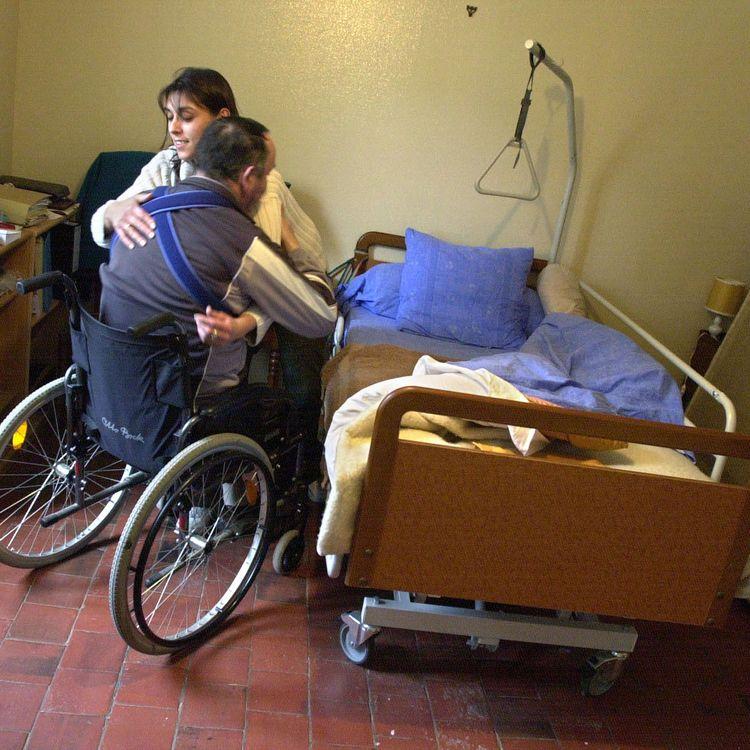 Une aide à domicile aide un homme hémiplégique à s'asseoir dans sa chaise roulante, le 7 février 2003, à Secqueville-en-Bessin (Calvados). (MYCHELE DANIAU / AFP)