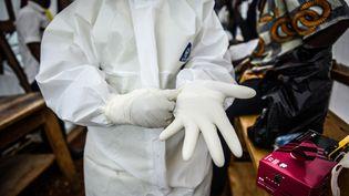 Une infirmière met des gants après avoir enfilé sa tenue de protection pour traiter des patients atteints du virus Ebola à Kenema (Sierra Leone), le 23 août 2014. (MOHAMMED ELSHAMY / ANADOLU AGENCY / AFP)