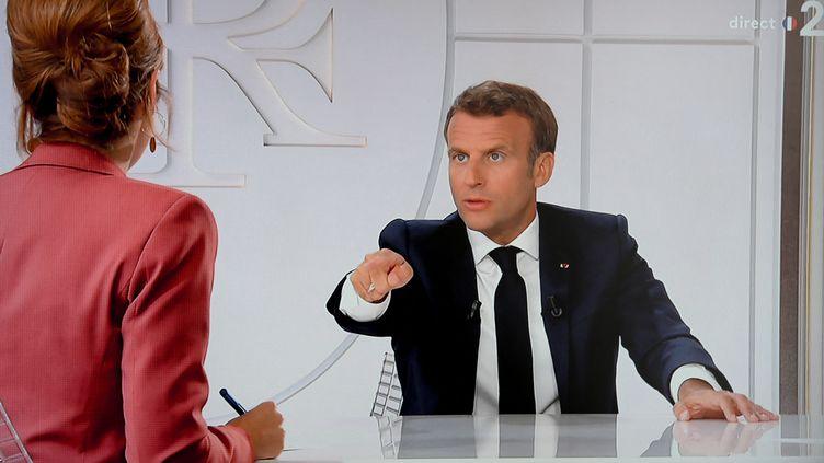 Vu d'un écran de télévision retransmettant l'interview du président de la République Emmanuel Macron depuis le palais de l'Elysée le 14 juillet 2020. (LUDOVIC MARIN / AFP)