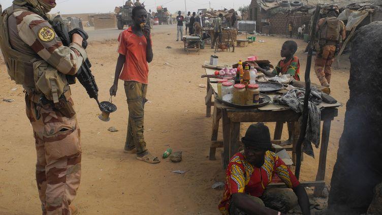 Militaire français de l'opération Barkhane en train de discuter avec un commerçant malien à Gossi (centre du Mali) le 25 mars 2019 (DAPHNE BENOIT / AFP)