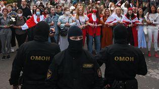 Des manifestantes à Minsk en Biélorussie le 29 août 2020, surveillées par des membres des forces de police. (EVGENY ODINOKOV / SPUTNIK / AFP)