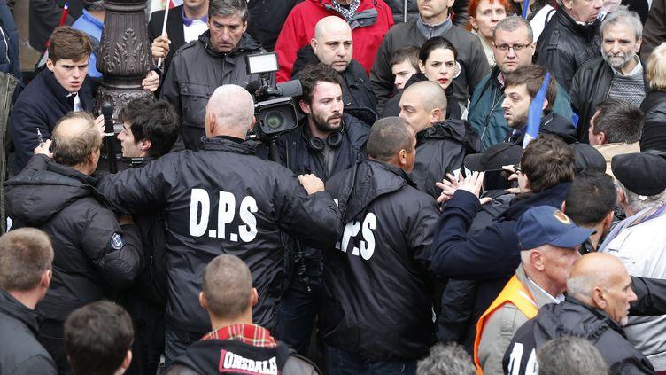 """Une équipe de l'émission du """"Petit Journal"""" de Canal+, prise à partie par des militants du FN à Paris, le 1er mai 2015. (THOMAS SAMSON / AFP)"""